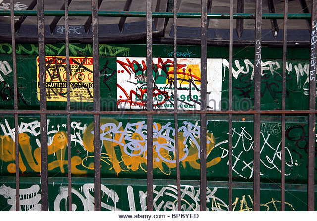 dumpster-with-graffiti-behind-metal-gate